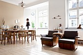 Bequeme Sessel mit braunem Lederbezug, seitlich Essplatz mit Armlehnstühlen aus Holz in offenem Wohnraum mit traditionellem Flair