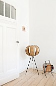 Retro floor lamp with spherical lampshade of wooden slats and magazine rack in corner