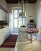 Fitted kitchen with corrugated metal doors and futuristic extractor hood above hob on island counter with integrated glass table