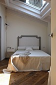 Double bed with headboard in narrow, renovated attic room with skylight