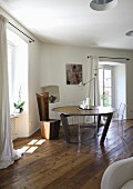Round, modern table and extravagant chair in corner of room with rustic wooden floor