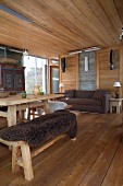 Rustic chalet interior; dining area with dark animal-skin blanket on bench and comfortable sofa next to sliding glass door in background