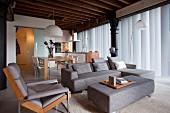 Loungebereich mit grauem Sofa und passendem Polster-Couchtisch, dahinter Essplatz in eleganter Loftwohnung