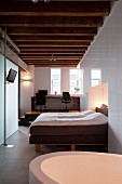 Bathtub in bedroom and double bed in niche formed by white fitted wardrobes; view of office on platform in elegant, renovated loft apartment