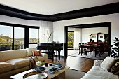 Luxurious interior with panoramic window, sofa set around coffee table, wide, open doorway with black frame and view into dining area