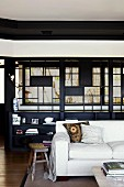 White sofa in front of dark shelves below Japanese-style lattice structure