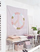 Hand-sewn, pastel wall hanging with peace motif above vintage bench with scatter cushions