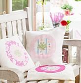 Handgenähte Kissen mit verschiedenen Mustern und Applikationen auf Holz-Gartenstuhl