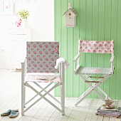 Make-over - two white directors' chairs with new floral covers in front of green wooden wall