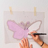 Delicate, lilac, stencilled pattern on wall - hand-crafted butterfly stencil, woman's hands and paintbrush
