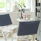 Hand-sewn, dark blue loose covers with white polka dots on two white, wooden folding chairs