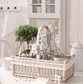 White-painted wicker basket with letter ornaments hanging from handle and crocheted trim on white kitchen table