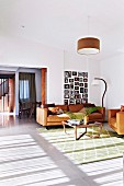 Cognac leather sofa set, wood and glass coffee table, gallery of pictures and vintage lamps in retro interior