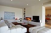 Wohnraum mit weißem Designersofa und Coffeetable-Set vor Kaminwand mit integrierten Regalnischen; umlaufend eine gemauerte Ablage