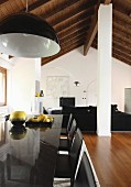 Pendant lamp above glossy, black dining table in open-plan interior with rustic wood-beamed ceiling