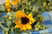 Sunflowers & hop tendrils on checked cloth