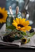 Glas für Besteck dekoriert mit Sonnenblumenblüte