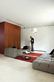 Grey, modern sofa set and man standing next to white arc lamp in minimalist lounge area