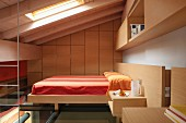 Bedroom in converted attic with custom wooden cabinets around double bed with orange bed linen
