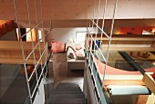 View from mezzanine down staircase with wire mesh balustrade into open-plan living room with beanbag and sofa