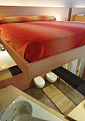 Double bed with orange and yellow bed linen on glass panel floor with view into contemporary bathroom below