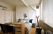 Desk at foot of bed against white, wooden wall in rustic, modern bedroom with closed louver blinds on windows