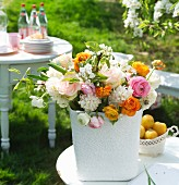 Colourful spring bouquet with ranunculus of various colours and white lilac on garden table