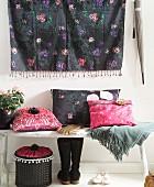 Kissen mit selbstgemachten Bezügen im Folklore-Hippie-Look auf Holzbank vor Wandbehang