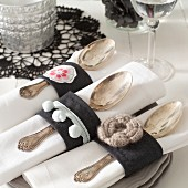 Hand-sewn napkin rings made from black fabric with appliqué flowers holding linen napkins and silver spoons