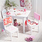 White, children's table and chairs painted with numbers and with patterned, fabric backrest covers