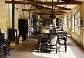 Partially renovated barn with rustic roof structure - Colonial-style dining set and kitchen area in open-plan interior
