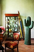 Oversize pencils leaning against display case of globes and cactus sculpture in period apartment