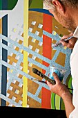 Artist with paintbrush and paint pot finishing a colourful graphic mural
