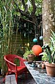 Rot lackierter Korbsessel und Topfpflanzen auf Steinplatte in kleinem Innenhof, im Hintergrund bunte Anhänger an Ästen