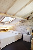 Purist bedroom under sloping attic roof with white-painted wooden structure; retro lamp on bedside table and partial view of vintage figure to one side