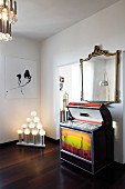 Retro Musikbox unter Spiegel mit antikem Goldrahmen, moderne Kunst und ausgefallene Leuchtobjekte im Wohnraum