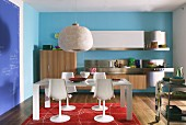 Dining area with tulip chairs in front of minimalist, designer kitchen with floating, wooden base units, stainless steel elements, blue and red colour scheme and blue blackboard wall