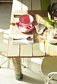 Place setting in mixture of styles on rustic, vintage-style board table with traces of paint