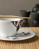 Chopsticks and china bowl with brown leaf motif on bamboo placemat