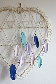 Colourful, modelling compound feathers hanging from wire heart as wall decoration