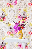 Anemones, ranunculus and orchids in yellow, floral vase against floral wallpaper