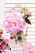 Pink peonies, lantana flowers and costume jewellery on miniature wire tailors' dummy