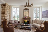 Sofa set and armchairs in comfortable lounge area in various shades of brown in traditional interior