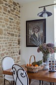 Dining area with white cushions on wrought iron chairs and basket of fruit and vase of hydrangeas on table
