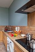 Küchenzeile mit Arbeitsplatte und Schrankfronten aus Holz, an hellblau getönter Wand