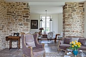 Sofa and armchair in modernised, rustic interior with stone wall and view of dining area through floor-to-ceiling open doorway
