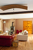 Red leather couch and pale couch in living room with wooden floor and wood-burning stove in renovated country house