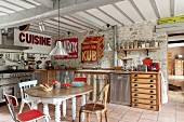 Chairs of various styles around oval wooden table in dining area of rustic, open-plan kitchen decorated with vintage metal advertising signs