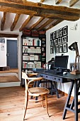 Thonet armchair at black desk in rustic interior with wooden ceiling