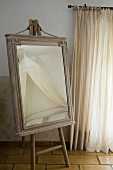 Dressing mirror in old cabinet top frame on painters' easel in Provençal bedroom